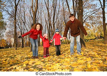 father and mother with the children in the park in autumn