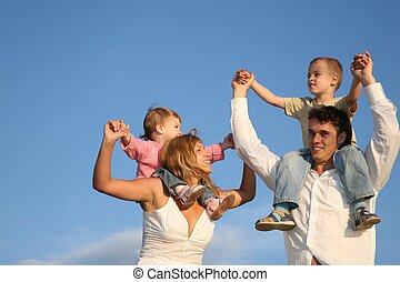 father and mother with the children on the shoulders