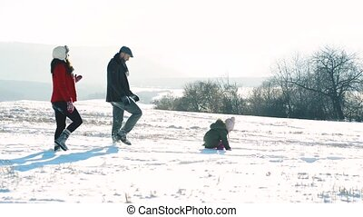 Father and mother with their daughter, walking in the snow....