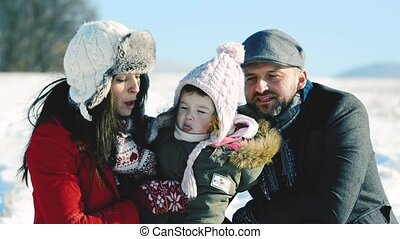 Father and mother with their daughter, winter day. - Father...