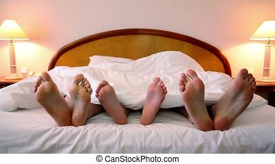 Father and mother with their son lay in bed under blanket and move shoeless feet