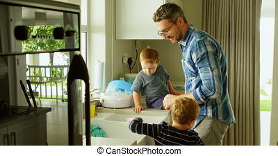 Father and siblings cleaning kitchen sink 4k - Father and...