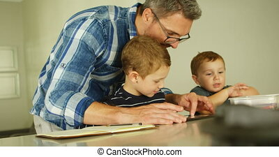 Father and siblings using digital tablet in living room 4k -...