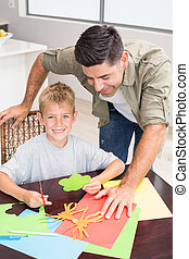 Father and smiling son making paper shapes together at the table at home in kitchen