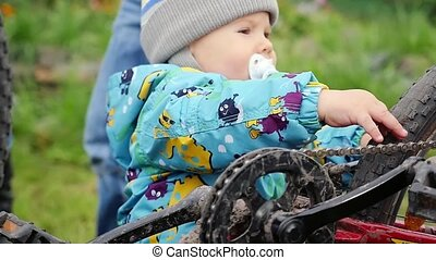 Father and Son, 1 year old boy, are spending quality time together fixing a bike sitting on grass. Slowmotion. 1920x1080