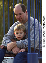 A father and son casually posed in the park.