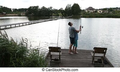 Father and son angling at tranquil lake in summer