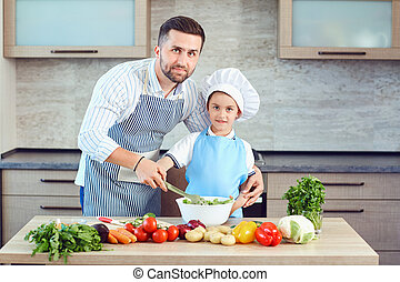 Father and son are cooking in the kitchen