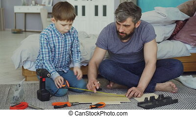 Father and son are measuring piece of wood with measure-reel...