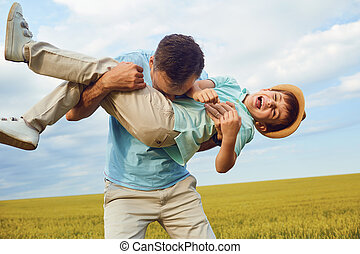 Father and son are playing in the field.
