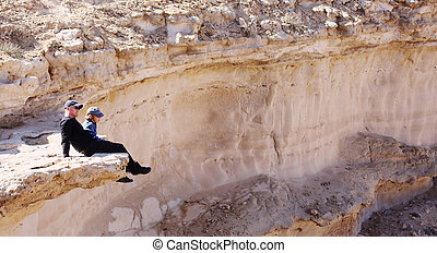 Father and son are sitting on a cliff