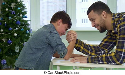Father and son armwrestle on the table