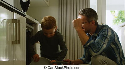 Father and son arranging plate in modular kitchen cabinet 4k...