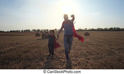 Father and son as superheroes running across field