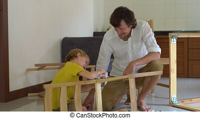 Father and son assemble wooden furniture from small parts. Little boy helps his father to assemble a chair.