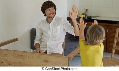 Father and son assemble wooden furniture from small parts. Little boy helps his father to assemble a table. Man and boy give each other five after finishing a table assemble.