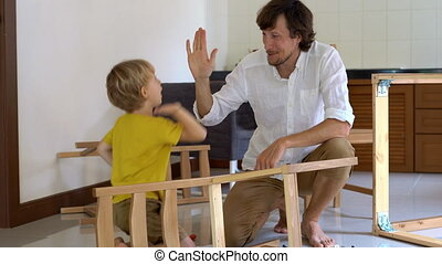 Father and son assemble wooden furniture from small parts. Man and boy give each other five after finishing a chair assemble.