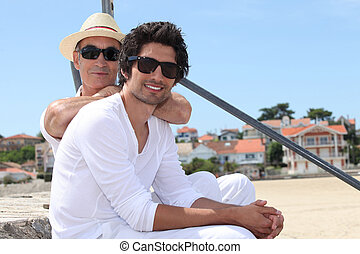 father and son at beach wearing sunglasses