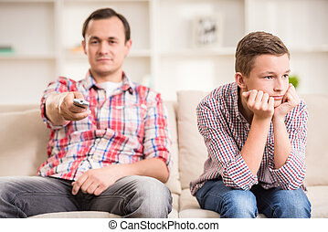 Father and son at home - Boy sitting at sofa and get bored...