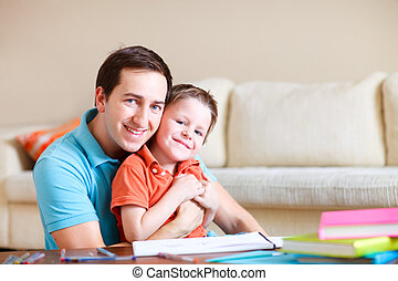 Father and son at home - Young father and his son drawing...