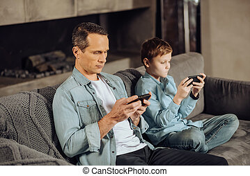 Father and son being glued to their phones