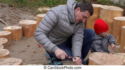 Man making round obstacle course with stepping logs of various height while kid playing nearby