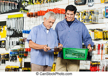 Father And Son Buying Tools In Hardware Store - Father and...