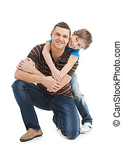 Father and son. Cheerful father and son standing close to each other and smiling while isolated on white