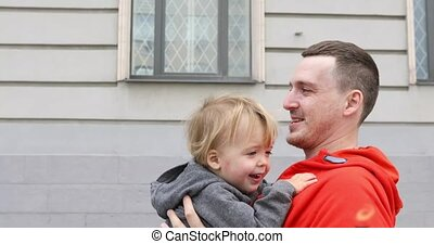 Father And Son Cuddling Together on a street. Dady throws...