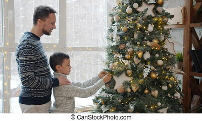 Father and son decorating New Year tree hanging bright balls and talking at home