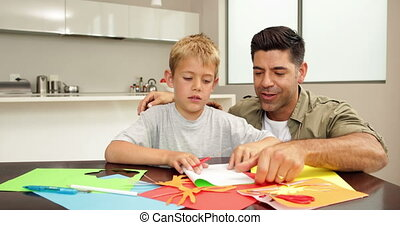 Father and son doing arts and crafts at kitchen table at ...