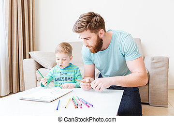 Father and son drawing in living room at home