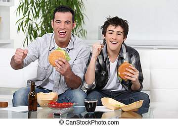 Father and son eating burgers in front of TV