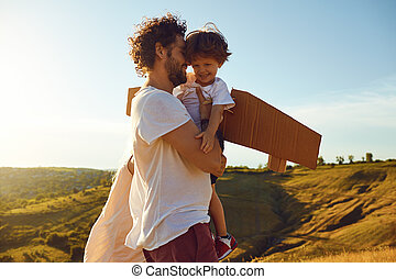 Father and son embrace in nature at sunset