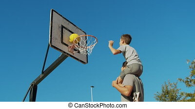 Father and son enjoy a playing basketball.
