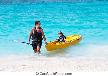 Father and son enjoying a kayak ride on a troical beach