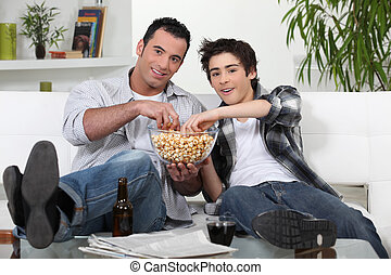Father and son enjoying a movie night together