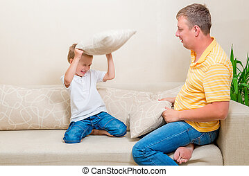 father and son fighting pillows on the couch