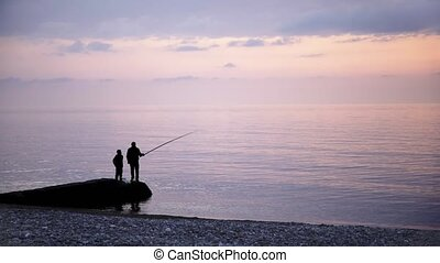 Father and son fishing at a sea shore