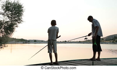 Father and son fishing at dusk by the lake