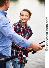 Father and son fishing on river - Glad father and teenager ...
