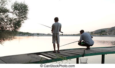 Father and son fishing on the lake shore at dusk in the summer
