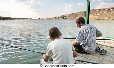 Father and son fishing on the lake shore in the summer