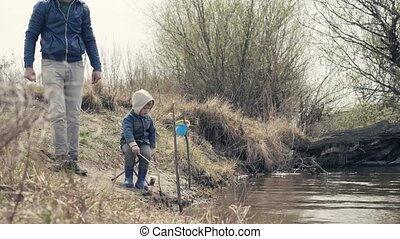 Father and son fishing together on river. Little boy with fishing rod on shore
