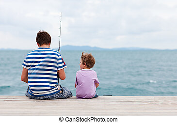 Father and son fishing together - Back view of father and...