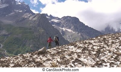 Father and son go along the glacier up to the mountain peaks. They travel together.