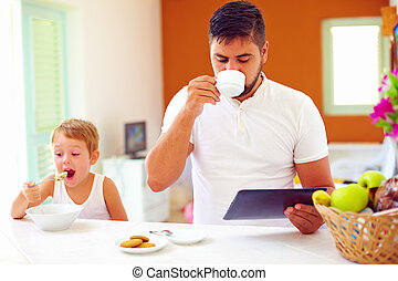 father and son having breakfast in the morning at home kitchen