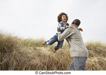 Father And Son Having Fun In Sand Dunes