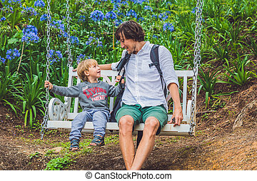 Father and son having fun on swings in a flower garden