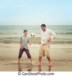 Father and son having fun on the beach with a ball